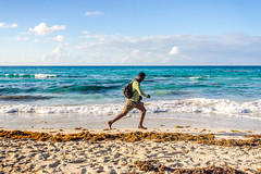 While everybody on the beach is relaxing, this chap runs by like he stole running.