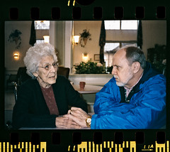 Struggle To Remember (Anne Worner) Tags: old family man love film analog 35mm table 50mm holding candid photojournalism lobby elderly scanned caring alzheimers agfa visiting manualfocus empathy nursinghome 400iso forgetting pentaxme colorfilm agfaoptima400 filmedge pentax50mm14 anneworner