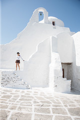 Woman in a white-washed Greek church (envylight) Tags: travel summer vacation house building tourism sunshine architecture facade island greek mediterranean exterior painted traditional sightseeing cottage aegean property style greece tropical paving mikonos whitewash