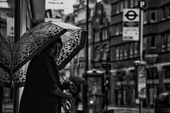 IMG_7578-Edit (roger_thelwell) Tags: life street city uk winter portrait england people urban bw white black streets cold london wet lamp monochrome westminster beauty hat rain leather mobile umbrella hair bag walking real photography mono chat shiny phone traffic post natural photos britain circus cigarette candid cab taxi great over sac hats cell photographic smoking lamppost photographs oxford conversation shiney talking shoulder handbag stud speak speaking studs commuters scak