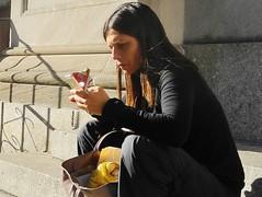 power lunch (omoo) Tags: newyorkcity sunlight girl cellphone streetscene lunchhour powerbar lightandshadow ourladyofpompeii prettygirl greenwichvillage powerlunch churchsteps carminestreet dscn5759 longstraighthair carmineandbleecker powerbarandcellphone
