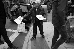 Overlooked (nstoop) Tags: people newyork news blackwhite flyer chinatown small streetphotography busy tall hardjob