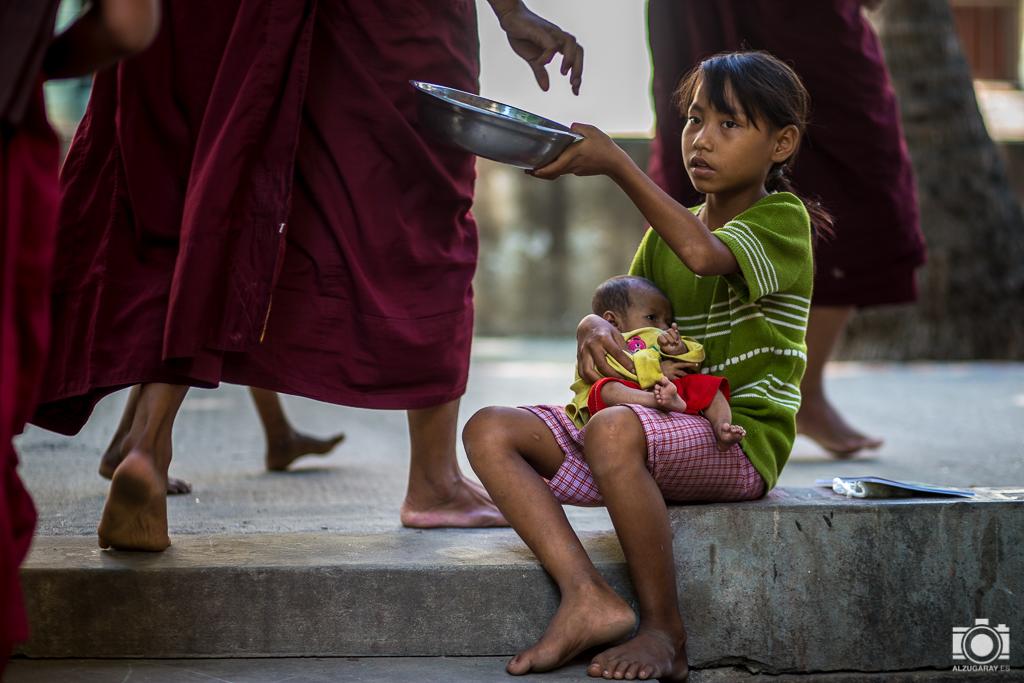 Niña con su hermano en brazos pidiendo en el Monasterio de Mahagandayon