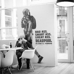 Poster boy (halifaxlight) Tags: street bw woman norway poster square table waiting sitting superhero bergen marvelcomics deadpool charirs