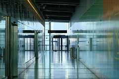 Corridor reflection (fabiankoppers) Tags: door morning travel blue light sunlight color colour reflection green abandoned industry glass wall architecture copenhagen airport pretty pattern open empty corridor indoor walls facility depth vast