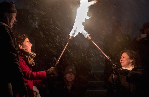 Governor Gina Raimondo passes the flame to Secretary of State Nellie Gorbea. Photo by Jen Bonin.
