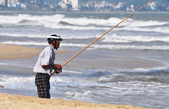 All that fresh air... (Roving I) Tags: ocean sea beach sand surf smoking vietnam recreation cigarettes rods protection danang helmets surfcasting