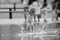 Dancing in the rain.... (Marie.L.Manzor) Tags: street city people bw white black paris france cute water girl monochrome childhood silhouette fun kid nikon focus dof child bokeh candid joy moment nikkor chlidren bokek marielmanzor nikon610