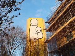Stik Street Art in Acton (DJLeekee) Tags: uk baby streetart building london yellow graffiti sticks stickman acton towerblocks stik