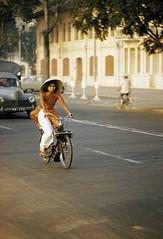 SAIGON 1961 - Cô gái chạy xe Vélo Solex. Photo by Wilbur E. Garrett (manhhai) Tags: color vietnam chi minh adult|young culture|traditional person|young image|day|outdoors|photography|vietnam|south vietnam|saigon|ho city|one women|vietnamese ethnicity|vietnamese clothing|ao dai|non la|commuter|bicycles|motorbikes|blurred motion|urban life|vertical