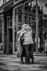Tippy toe hug (tootdood) Tags: street blackandwhite reflection window shop manchester hug market fromthehip streetcandid canon70d tippttoe