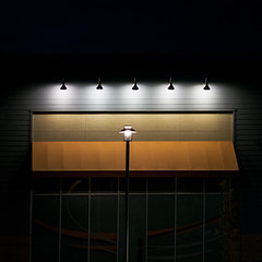 the night lights are bright, but pole's alone (MyArtistSoul) Tags: ca urban orange monochrome yellow night square awning lights minimal lamppost storefront stark vignette asymmetrical 6840 oxnard s100 thecollection