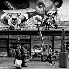 Artist at work.. (Akbar Simonse) Tags: street people urban bw sculpture streetart holland blancoynegro netherlands monochrome women zwartwit candid nederland streetphotography sculptuur denhaag bn squareformat scarves haag virus thehague mediamarkt beeld artistatwork vierkant lahaye sgravenhage agga straatfotografie dscn2711 akbarsimonse hoogwerler maniverhuur
