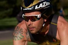 Second Leg (Cathy de Moll) Tags: bike biker race racer triathlon closeup face sweat concentration tattoo speed portrait