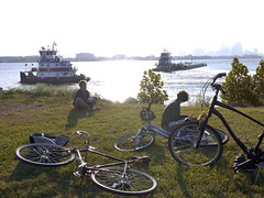 Tim and Michele, New Orleans (tomtomklub) Tags: camera city blue autumn trees friends urban woman white man reflection green fall water grass skyline landscape boats flow photography glasses canal louisiana industrial afternoon tour cross bright weekend background neworleans young relaxing bikes sunny bicycles adventure holy southern dirt mississippiriver overexposed late tugboat barge slope helmets laying levee lowerninthward