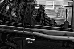 Beautiful girl in a taxi    IMG_8530-Edit (roger_thelwell) Tags: life street city uk winter portrait england people urban bw white black streets cold london lamp monochrome westminster beauty hat rain leather mobile umbrella hair bag walking real photography mono chat shiny phone traffic post natural photos britain circus cigarette candid cab taxi great over sac hats cell photographic smoking lamppost photographs oxford conversation shiney talking shoulder handbag stud speak speaking studs commuters scak beautifulgirlinataxi