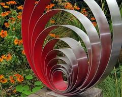 The Metallic Spiral (Dazzygidds) Tags: lighting red sculpture spiral metallic nationaltrust warwickshire orangeflowers coughtoncourtgardens