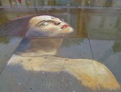 face on a wet pavement (helenoftheways) Tags: uk london rain artwork faces pavement trafalgarsquare greeneyes redlips artistunknown