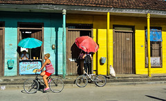 Cycling in the city ... (Kat-i) Tags: street colorful cuba shops kati umbrellas bunt kuba geschfte 2014 schirme radfahren baracoa guantnamo strase cacling nikon1v1