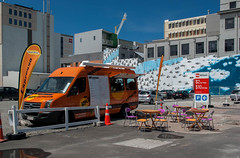 Colouful Setting (Jocey K) Tags: pink newzealand christchurch sky orange signs streetart architecture buildings painting penguins mural chairs crane tables foodvan