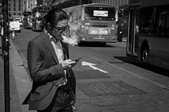 Exhaust Gasses (Leanne Boulton) Tags: life street city uk light shadow portrait people urban blackandwhite bw cloud white man black detail male texture monochrome face mobile canon 50mm mono scotland living blackwhite phone natural humanity outdoor expression glasgow candid smoke culture streetphotography streetlife scene smoking depthoffield business suit human shade 7d posture gesture smoker society tone facial vapour exhaling vape candidstreetphotography vaping