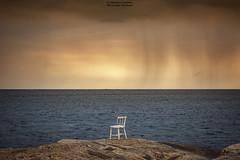 Watching The Rain (Fredrik Lindedal) Tags: ocean chair rocks red rain coast nikon onewithnature fredriklindedal water clouds cloud alone sweden sverige sky skyline art seascape outdoor shore landscape