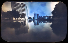 Puddles Transformed into Oceans (batuda) Tags: pinhole obscura stenope lochkamera analog analogue tin altoids film photocopy paper mediumformat 6x9 roundedcorners wideangle lowangle d76 color colour toned city cityscape building architecture tree trees sky ground water puddle pool flood street reflection wet kaunas lithuania lietuva