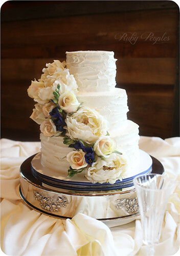 """A buttercream wedding cake with a cascade of silk flowers • <a style=""""font-size:0.8em;"""" href=""""http://www.flickr.com/photos/50891271@N03/16162033147/"""" target=""""_blank"""">View on Flickr</a>"""