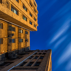 Looking Up early 20th Century Art Deco Architecture in Brighton Neighborhood Boston with Blue Sky and Gold Light (Greg DuBois Photography) Tags: city longexposure blue winter light shadow sky urban usa sunlight motion building yellow boston skyline architecture facade contrast canon photography gold movement brighton day cityscape unitedstates vibrant massachusetts newengland wideangle bluesky lookingup lookup aberdeen nd daytime artdeco dramaticsky lightandshadow brickbuilding winterlight afternoonlight abstractarchitecture goldenlight fairweather goldlight ndfilter residentialbuilding cloudmovement brightonarchitecture daytimelongexposure neutraldensity artdecoarchitecture bostonarchitecture extremeexposure leefilters brightonmassachusetts bostonphotography canon6d massachusettsarchitecture cloudmotion bostonneighborhood graphicarchitecture leebigstopper gregdubois gregduboisphotography bostonartdeco aberdeenartdeco aberdeenboston