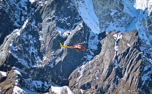 Helicopter is flying between snow mountains peak in high Himalayan mountains , Nepal