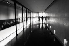 event horizon lies ahead (Super G) Tags: california light people blackandwhite bw woman man motion blur walking losangeles unitedstates corridor tunnel passage intentional nikon266