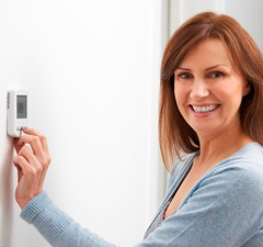 Smiling Woman Adjusting Thermostat On Home Heating System (eiklimlendirmesistemleri) Tags: thermostat house home indoors cold woman heat energy energyefficiency radiator fuelandpowergeneration savings adjusting winter electricity centralheating heating environmentalconservation energyconservation savingenergy budget fuelefficiency debt energycrisis homefinance forties 40s mature caucasian horizontal copyspace oneperson person people happy smiling portrait lookingatcamera humanface