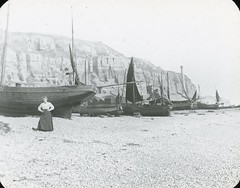 H01274 Hastings fishing beach (c.1900) (East Sussex Libraries Historical Photos) Tags: beach boats costume library victorian cliffs shore mast hastings fishingboats easthill fishingbeach magiclanternslide