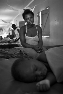 A young mother watches over her baby in the hospital who has malaria.