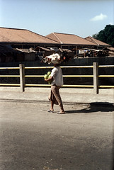 24-629 (ndpa / s. lundeen, archivist) Tags: city people bali woman color film 35mm buildings indonesia town village basket sandals candid nick citylife streetphotography pedestrian southpacific balance 24 1970s 1972 balancing indonesian carry carrying balinese dewolf oceania pacificislands nickdewolf photographbynickdewolf onherhead reel24