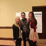 Three students pose together during history capstone poster presentations.