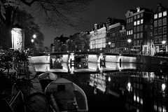 There's no place like Amsterdam (McQuaide Photography) Tags: old city longexposure nightphotography bridge light blackandwhite bw house holland reflection building history water netherlands monochrome dutch amsterdam bike architecture night zeiss outside mono licht boat canal blackwhite still europe nacht outdoor sony traditional tripod transport nederland peaceful oldbuildings calm historic brug fullframe alpha huis singel residential oud tranquil stad authentic manfrotto noordholland gebouw gracht c1 huizen canalhouse 1635mm northholland grachtenpand phaseone variotessar captureone mirrorless sonyzeiss mcquaidephotography a7rii ilce7rm2 captureonepro9