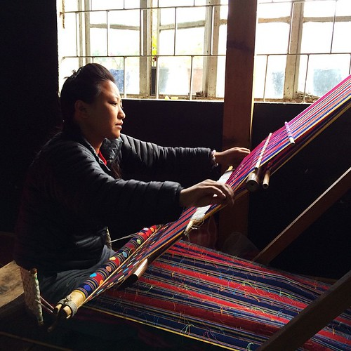 Lady weaving delicate and complex patterns for textile that are used to make traditional Bhutanese costumes.
