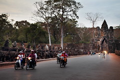 Angkor 30 (gsamie) Tags: road sunset people orange blur canon temple gate cambodia bokeh buddha ruin motorcycles carving depthoffield angkor buddhas angkorthom t3i 600d gsamie guillaumesamie