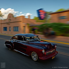 Taos Low Rider passing by The Historic Taos Inn (JMichaelSullivan) Tags: newmexico 100v 10f badge 600v taos 200v lowrider enchantment 500v 700v 300v 5f 15f 1000v 400v 900v 800v