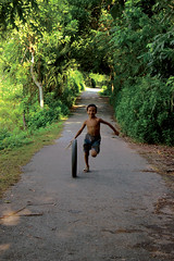 Everything is ceremony in the wild garden of childhood (Synthia Mazumder) Tags: boy childhood wheel joy running laughter greentree