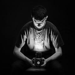 Another World In the Viewfinder (Tom Williamson1) Tags: world light portrait blackandwhite bw selfportrait monochrome self dark different looking flash tripod bronica ideas viewfinder selfie offcameraflash zenza triggers s2a strobist d7000 believeinfilm