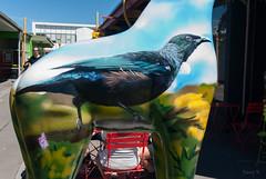 Walking on the Red Chair (Jocey K) Tags: newzealand christchurch sky people detail building bird art chair giraffe tui newbrighton painitng canterbuy standstall headinthecloudsfeetonthegroundeverywhereinbetweenandbeyondno39 giantfibreglassgiraffesculpture