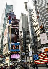 Skyscrapers of Manhattan (nrhodesphotos(the_eye_of_the_moment)) Tags: dsc07931300 wwwflickrcomphotostheeyeofthemoment nrhodesphotosyahoocom architecture manhattan billboards signs glass nyc perspective 42ndstreet metal crossroadsnyc people americanflag interactive skyline skyscrapers geometric shadow reflections buildings skyscraper outdoor building urban lightfixtures