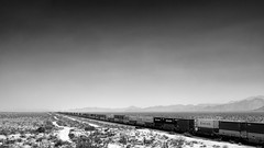 Crossing the big plains (Tommy Hyland) Tags: track rail engine bnw diesel locomotive speed horizen traffic container cargo road extreme delivery goods transportation bw far america business load railroad shipment logistic infrastructure desert industrial motion way industry usa travel highway 40transporttransitmountainblackandwhitephoto commercial power railway plane az train yucca long arizona steel heavy distant freight fujifilm xt1