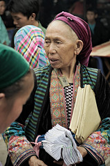 Elderly woman from an ethnic minority holding papers in Mo Vc market - H Giang Province - Vietnam (PascalBo) Tags: nikon d300 asia asie southeastasia asiedusudest vietnam vitnam vitnam vietnamese hgiang hagiang movc meovac market march people woman femme hilltribe ethnicgroup ethnie ethnic ethnicity minority headdress headwear indigenous costume outdoor outdoors pascalboegli