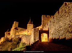 Carcassonne Porte d'Aude at Night (Edwinjones) Tags: old city travel light urban black france castle stone architecture night photoshop french ancient flickr view roman fort stonework sony picture culture sigma wideangle pic scene disney medieval nightime traveling dslr fortification chateau legend chteau carcassonne franais hdr highdynamicrange languedoc myth ville tourisme worldheritage topaz remparts walledcity adjust languedocroussillon fortified floodlights mdival photomatix lacit a700 tonemapping fortifiedcity portedaude dslra700 audegate