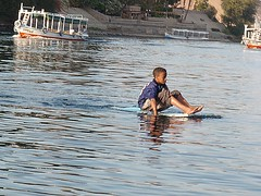 Nubian boy on the Nile (kriswoods2322) Tags: trip travel blue boy vacation river egypt floating nile stillwater nubian aswandam waterboard