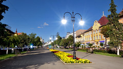 Trgu Mure town centre simultaneously at nighttime and daytime (lehellokodi) Tags: targu mures marosvasarhely neumarkt transylvania transilvania erdely ardeal romania siebenburgen daytime daylight midday afternoon night day nighttime evening lamp light lens flare outdoor road park flowers yellow red street trees wide angle bench blue sky multiple combined exposure superimposed overlay town simultaneous artificial lights trick shot cityscape time timeless