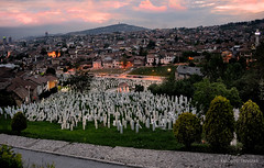 HISTORIC SARAJEVO (BOSNIA AND HERZEGOVINA, SARAJEVO) (KAROLOS TRIVIZAS) Tags: city cemetery lights town dusk sarajevo hill roofs civilwar tombs slope bosniaandherzegovina muslimcemetery muslimtombs sunsethouses
